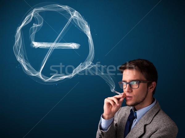 Młody człowiek palenia niezdrowy papierosów podpisania Zdjęcia stock © ra2studio