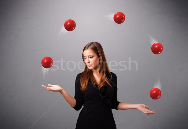Fiatal lány áll zsonglőrködés piros golyók csinos Stock fotó © ra2studio