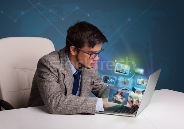 Attractive young man sitting at desk and watching his photo gallery on laptop Stock photo © ra2studio