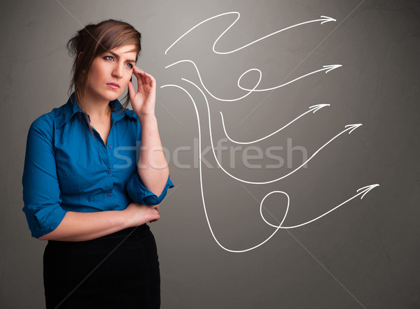Stock photo: Attractive teenager looking at multiple curly arrows