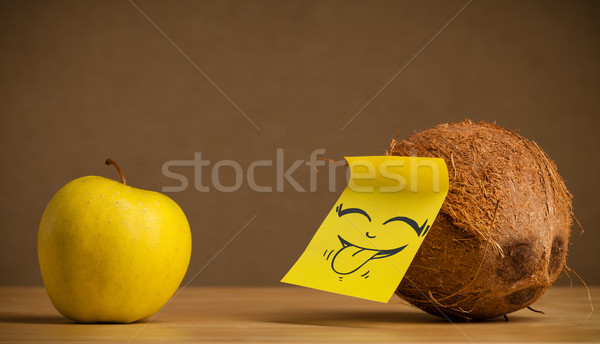 Coconut with post-it note sticking out tongue to apple Stock photo © ra2studio