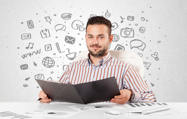 Young businessman with all kind of hand-drawn media icons in bac Stock photo © ra2studio