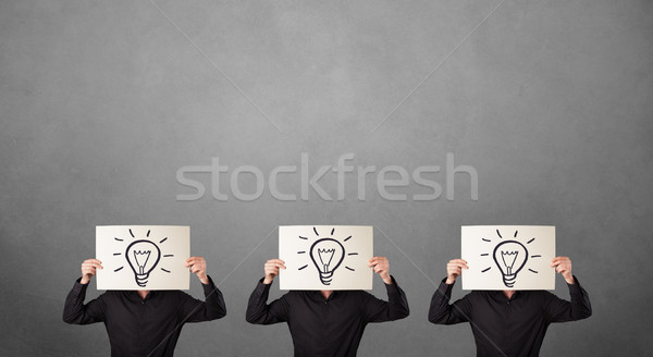 Men in suit gesturing with sketched lightbulbs on cardboard Stock photo © ra2studio