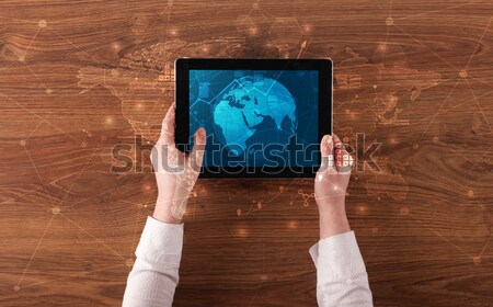 Hand holding tablet with global reports and stock market change  Stock photo © ra2studio