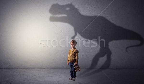Dinosaurus shadow behind cute boy Stock photo © ra2studio