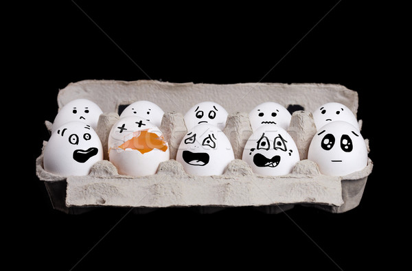 Group of smiley eggs in box with broken egg on black background Stock photo © ra2studio