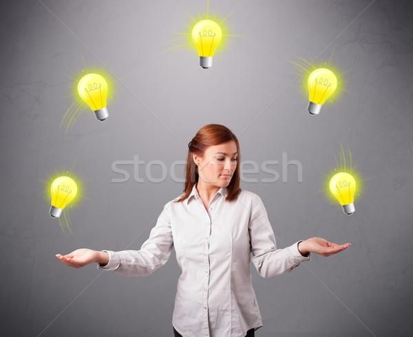 Fiatal hölgy áll zsonglőrködés villanykörték gyönyörű Stock fotó © ra2studio