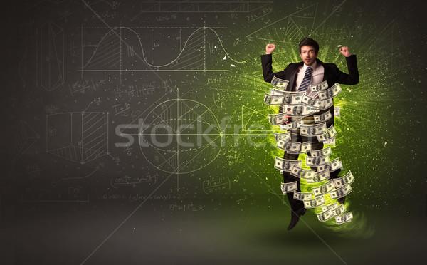 Cheerful businesman jumping with dollar banknotes around him Stock photo © ra2studio