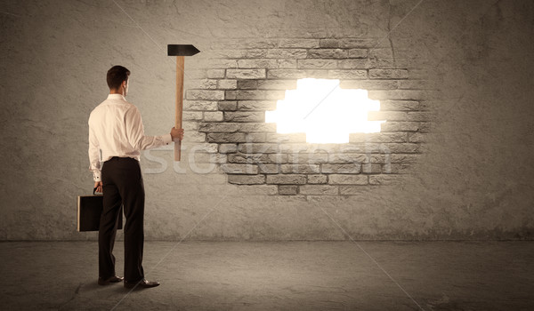 Business man hitting brick wall with hammer and opening a hole Stock photo © ra2studio