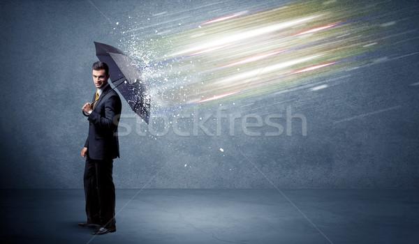Stock photo: Business man defending light beams with umbrella concept