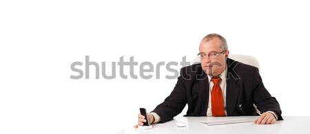 businessman sitting at desk and looking mobilephone with copyspace, isolated on white Stock photo © ra2studio