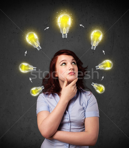 Stock photo: Young woman thinking with lightbulb circulation around her head