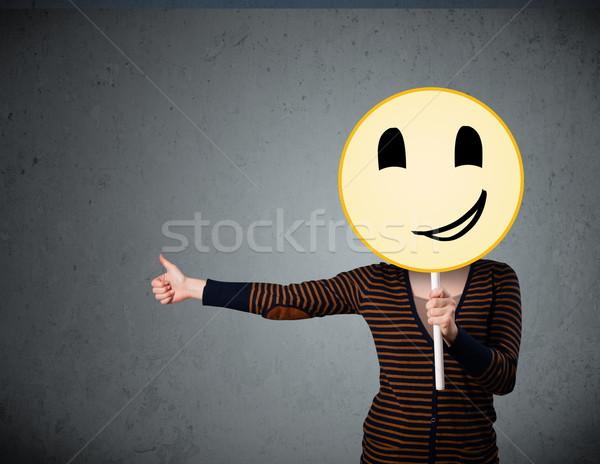 Fiatal nő tart mosolygós arc emotikon fiatal hölgy Stock fotó © ra2studio