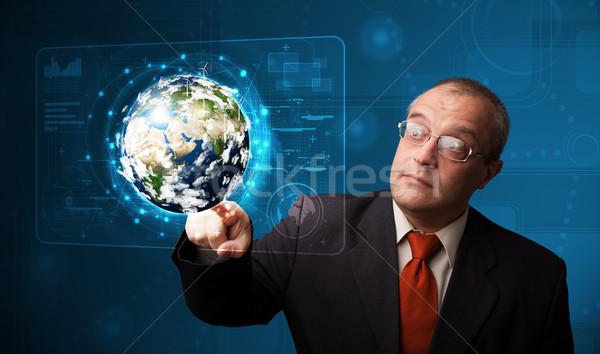 Businessman touching high-tech 3d earth panel Stock photo © ra2studio
