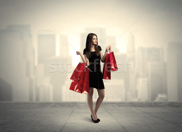 Elegant city girl with red shopping bags Stock photo © ra2studio
