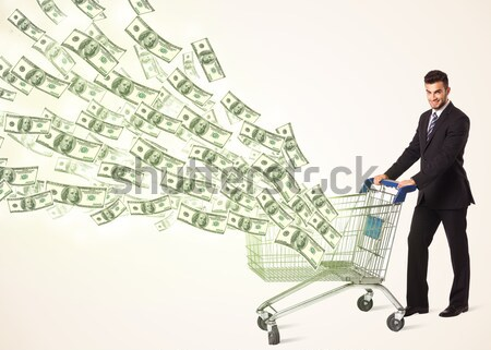 Stock photo: Businessman with shopping cart with dollar bills