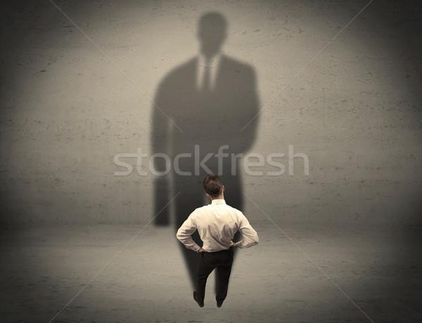 Businessman looking at big shadow concept Stock photo © ra2studio