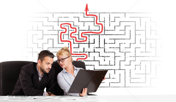 Business persons at desk with labyrinth and arrow Stock photo © ra2studio