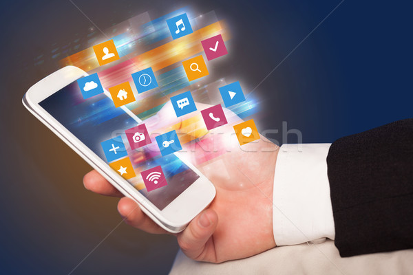 Stock photo: Hand using phone with colorful application icons and symbols con