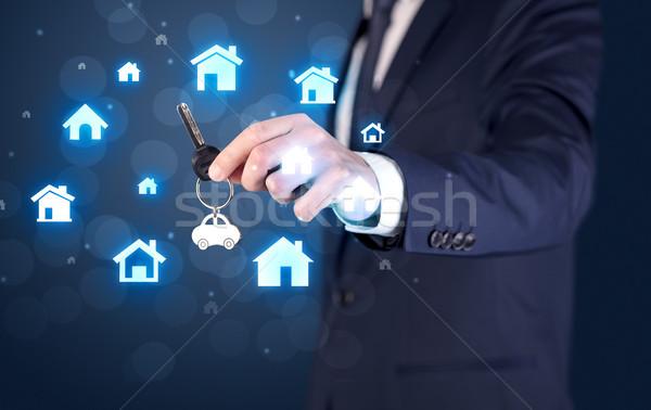 Businessman holding keys with houses around Stock photo © ra2studio