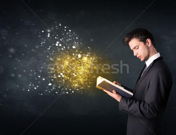 Młodych facet czytania magiczny książki tablicy Zdjęcia stock © ra2studio