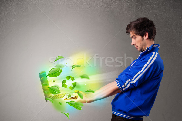 Casual young boy holding laptop with recycle and environmental symbols Stock photo © ra2studio