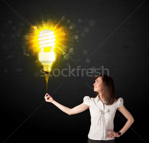 Businesswoman with an eco-friendly  bulb Stock photo © ra2studio