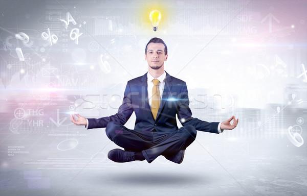 Businessman meditates with enlightenment concept Stock photo © ra2studio