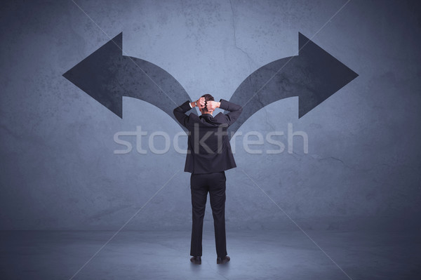 Businessman taking a decision while looking at arrows on the wall concept Stock photo © ra2studio