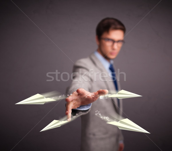 Handsome man throwing origami airplanes Stock photo © ra2studio