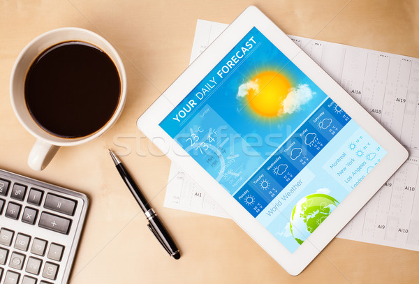 Workplace with tablet pc showing weather forecast and a cup of coffee on a wooden work table closeup Stock photo © ra2studio