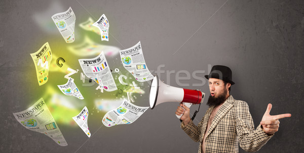Guy yelling into loudspeaker and newspapers fly out Stock photo © ra2studio