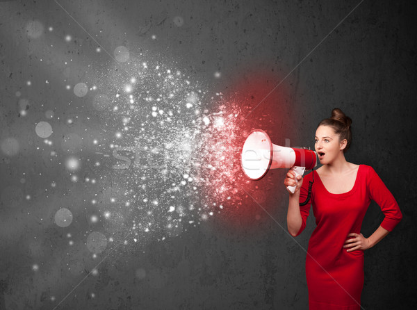 Woman shouting into megaphone and glowing energy particles explo Stock photo © ra2studio