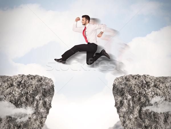 Funny człowiek biznesu skoki skał luka działalności Zdjęcia stock © ra2studio