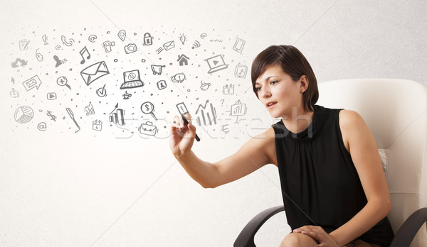 Stock photo: Young woman drawing and sketching icons and symbols