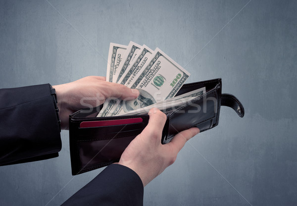 Stock photo: Hand in suit takes out dollar from wallet