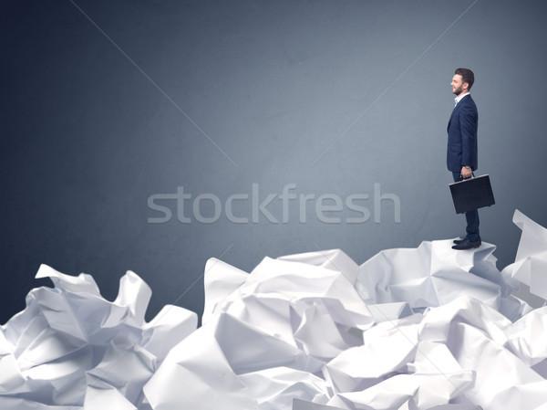 Businessman standing on crumpled paper Stock photo © ra2studio