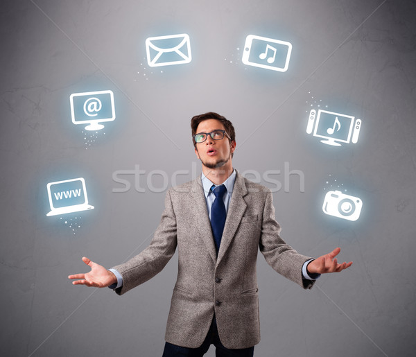 Stock photo: funny boy juggling with electronic devices icons