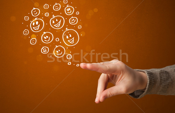 Group of happy smiley faces coming out of gun shaped hands Stock photo © ra2studio