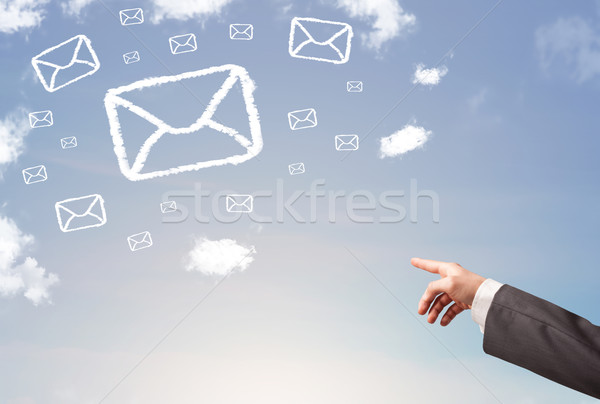 Hand pointing at mail symbol clouds on blue sky Stock photo © ra2studio