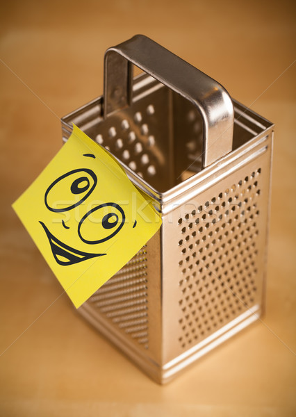 Post-it note with smiley face sticked on grater Stock photo © ra2studio