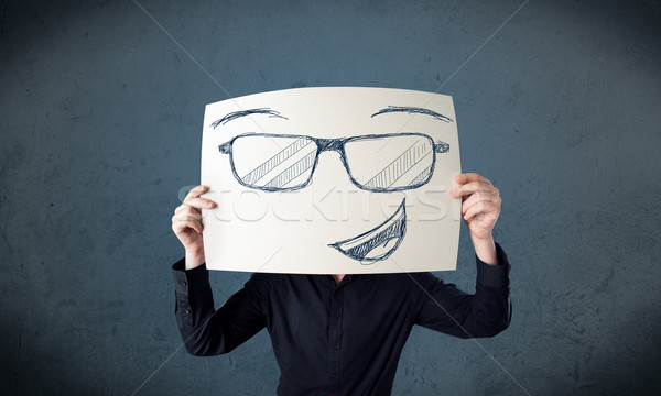 Businessman holding a paper with smiley face in front of his hea Stock photo © ra2studio