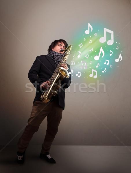 Jovem músico jogar saxofone notas musicais atraente Foto stock © ra2studio