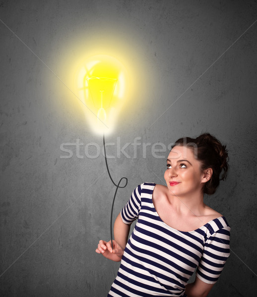 Woman holding a lightbulb balloon Stock photo © ra2studio