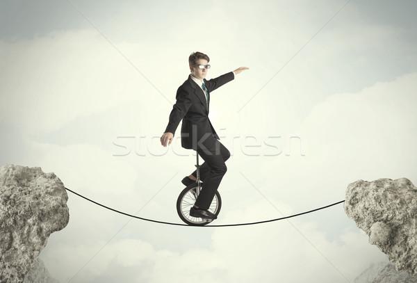 Trotzen Geschäftsmann Reiten Zyklus Klippen Business Stock foto © ra2studio