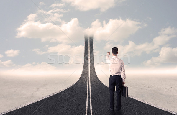 Stock photo: Businessman looking at 3d road that goes up in the sky