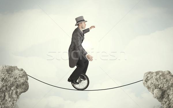 Bátor üzletember lovaglás bicikli sziklák üzletember Stock fotó © ra2studio