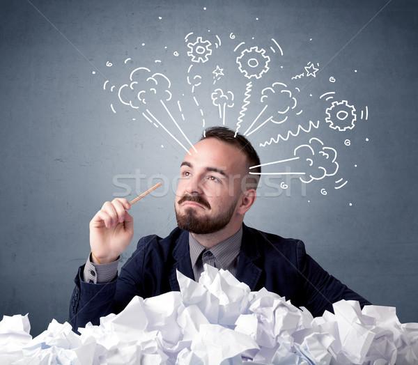 Biznesmen za papieru młodych posiedzenia rysunki Zdjęcia stock © ra2studio