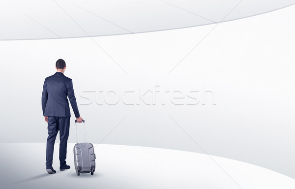 Businessman with suitcase walking in waiting room Stock photo © ra2studio