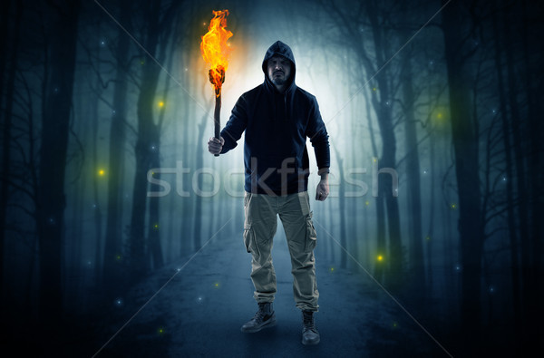Man coming from dark forest with burning flambeau in his hand co Stock photo © ra2studio